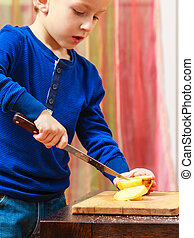 Child cut apple with a kitchen knife, cooking. - Child...