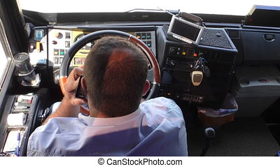 Bus driver talking on mobile phone - Rear above view of the...