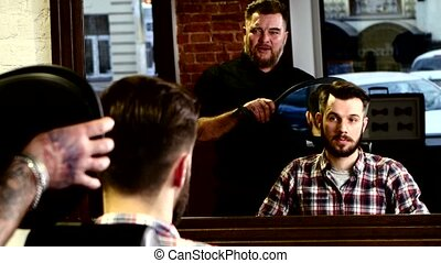 Barber reveals his client in mirror of new hairstyle. He is...