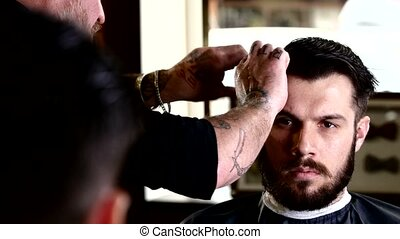 Barber performs a haircut with scissors and combs his client. Client while looking at herself in the mirror