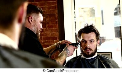 Truly stylish men's hairdresser: Master in tattoos performs a haircut with scissors to his client