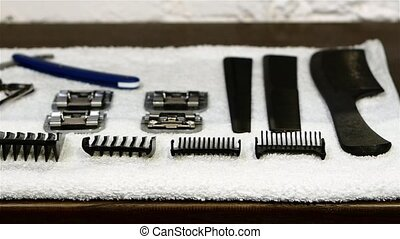 Barbershop: hairdresser's tools lying on a white towel. close up. Slow motion