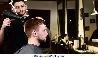 Stylish interior: Barber dries client hair - Barber stylish...