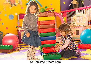 Two girls play with big bricks in playroom