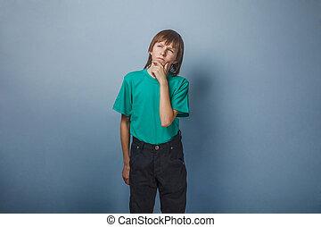 Boy, teenager, twelve years in green shirt , smiled dreamily...
