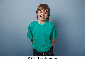 Boy, teenager, twelve years in a green shirt, closed his...
