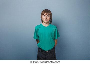 Boy , teenager, twelve years in green T-shirt , showing...