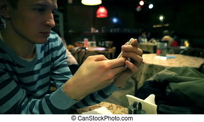 Young man using smartphone with cafe interior in background,...