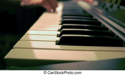 Electronic piano with keys in the foreground and hands of a...