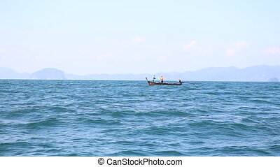 thai longtail boat in sea against islands - thai longtail...