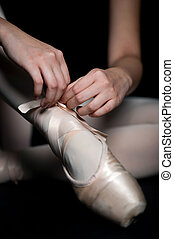Ballet Slippers - A ballerina tying her ballet slippers on,...
