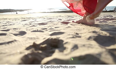 young blonde girl in sari walks along sand beach - european...