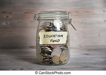 Money jar with education fund label - Coins in glass money...