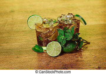 drink concept - cocktail with cola ice cubes and lime -...