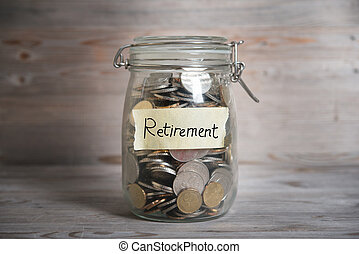 Money jar with retirement label. - Coins in glass jar with...