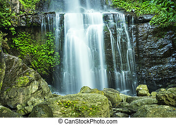 Pretty waterfall cascading over mountain rocks in lush green veg