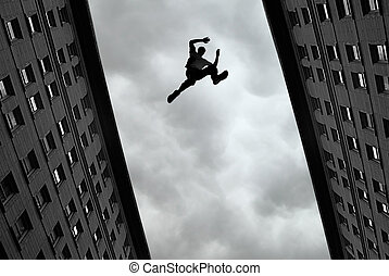 Man jumping from roof to roof - Man jumping over building...
