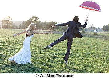 Catch me if you can - Married couple having fun on a field...