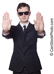 businessman in black suit and sunglasses showing stop, Isolated on white background