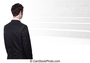 businessman looking at stairs - businessman in a black suit...