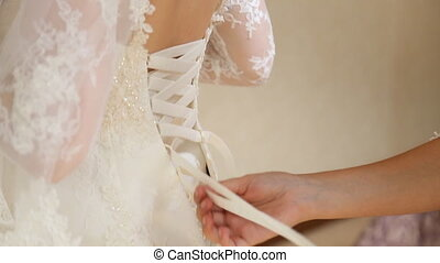 Dresses wedding dress - bridesmaid tying bow on wedding...