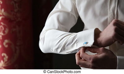 The groom wears a tie and cufflinks - Hands of wedding groom...