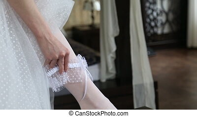 The bride wears a garter - Garter on the leg of a bride,...