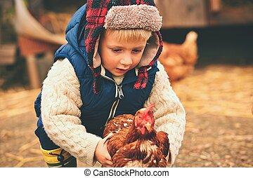 Little farmer - Little boy is holding the hen on the farm