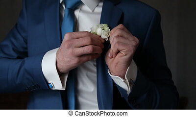 The groom wears boutonniere - Hands of wedding groom getting...