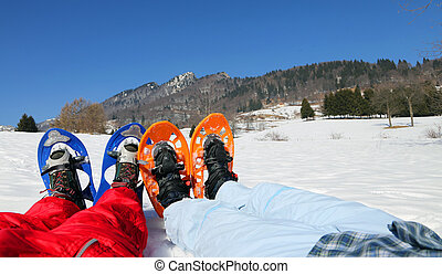 couple with blue and orange snowshoes in the mountains -...
