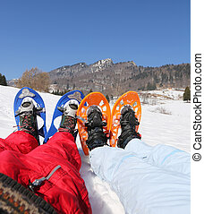 husband and wife with snowshoes in the mountains - husband...