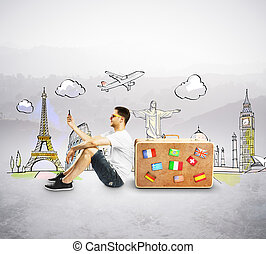 man with cellphone sitting near travel suitcase