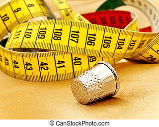 measuring tape and thimble - thimble against the...
