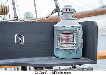 Old copper sailing boat's lamp on the bench on yacht