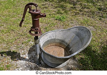 Old hand water pump and bath chair - A rusty old hand pump...