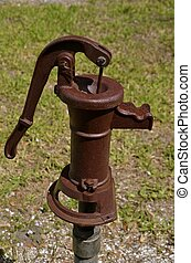 Old hand water pump - A rusty old hand pump is connected to...