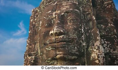 Giant stone face carved from stone at Bayon Temple, Cambodia...