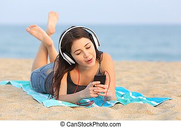 Teen girl listening music and singing on the beach - Teen...