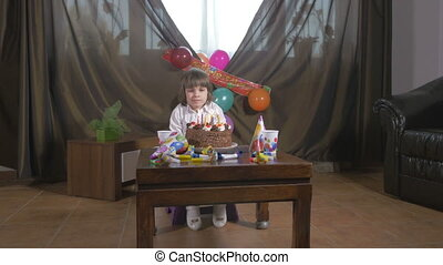 Young girl blowing candles