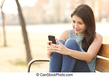 Teen girl using a smart phone sitting in a bench