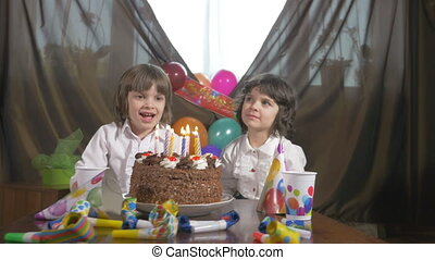Cute twin sisters blowing candles