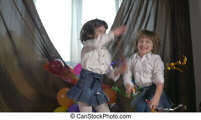 Sisters dancing at a birthday party - Young beautiful twin...