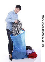 Elderly woman puts used clothes in a big bag isolated on...