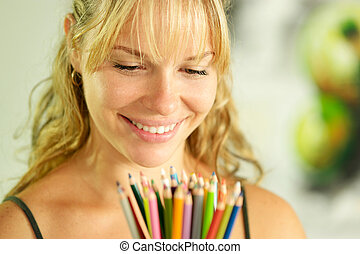Young female artist holding colored pencils and smiling -...
