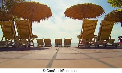 Deck Chairs and Thatched Umbrellas on the Beach - Deck...