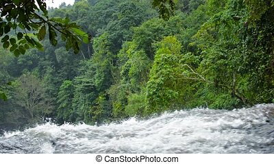 Raging Mountain Stream Cascades over a Natural Waterfall,...
