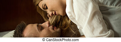 Couple in bed - Young attractive couple in love hugging in...