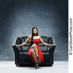 Young, beautiful and glamour woman in red dress sitting on...
