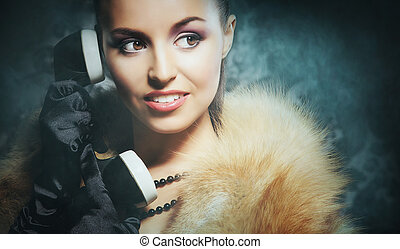Attractive young lady with the vintage phone over the retro...