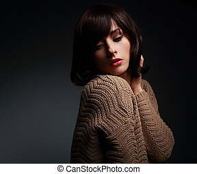Sexy makeup female model posing in warm wool sweater on dark...